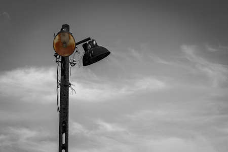 Old electric rusty metal street lamp on concrete lamppost - black and white image with selected color and copy spce