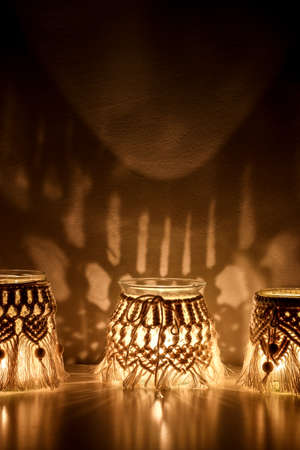 Macrame hand woven with cord three lanterns glow making abstract shadow patterns on the wall