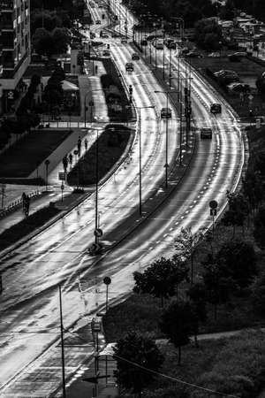 Black and white image of wide street in city wet and shining after rain