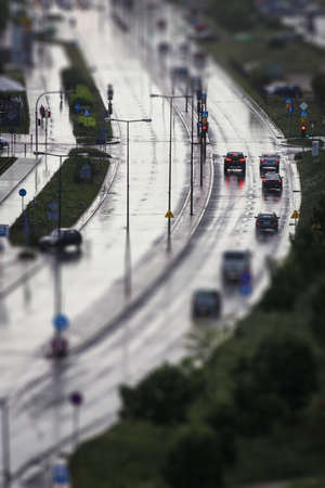 Cars wait on red traffic light on wet and shining street during rain, image with tilt shift effect makes scene looks like miniature Stock Photo