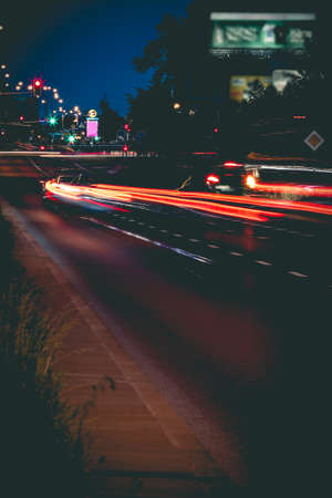 Wide street in residential district of Warsaw in evening with motion blurred lights of cars