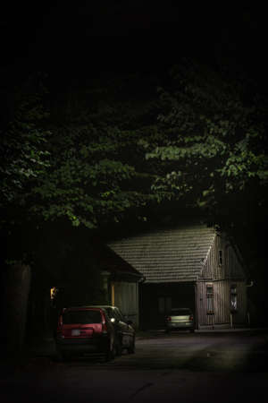 Old wooden house illuminated at the end of dark silent and empty street Imagens