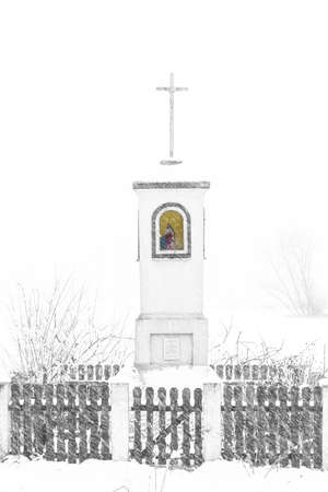 Old wayside shrine in polish countryside stand amid fields of snow in winter