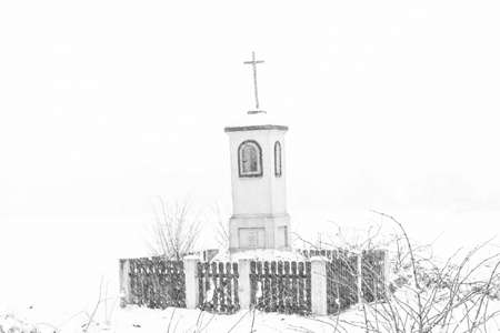 Old wayside shrine in polish countryside stand amid fields of snow in winter Archivio Fotografico