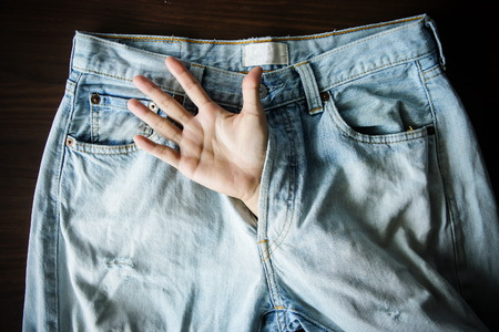 Hand inside jeans is meaning sexual Stock Photo