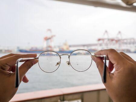 Frauenhand und Brille im Retro-Stil, die alle mit Wassertropfen auf der Linse bedeckt sind. Regenzeit