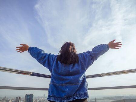 vrouw die naar de lucht kijkt en zich gelukkig of gelukkig voelt of missiesucces en steekt zijn handen op. Ze is blij en tevreden Stockfoto
