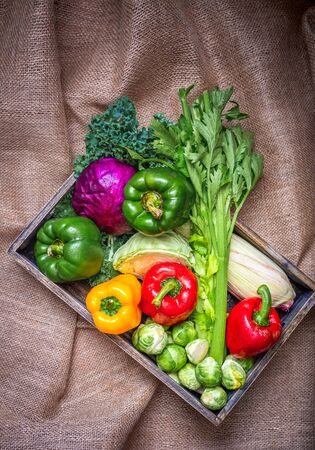 Various non-toxic fresh vegetables are placed in a wooden box placed on a mat. Many vegetables are purple and green sprouts, red pepper Yellow and green, Corn and others