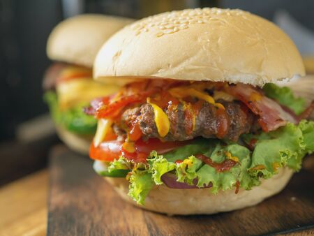 Homemade burgers with beer and cola made of bacon, pork, tomato, lettuce, onion, cheese and spices on wooden background