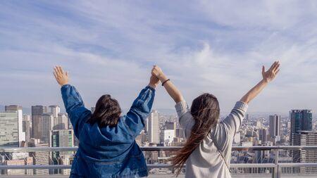 Vista trasera amigo cercano mirando al cielo sintiéndose afortunado o feliz o el éxito de la misión y levanta las manos. Ella esta feliz y contenta