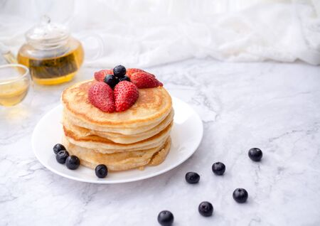 Stack of pancakes with topping, strawberry and blueberry.Placed in a white plate on a marble table and copy space.Eat with tea in the glass. Zdjęcie Seryjne
