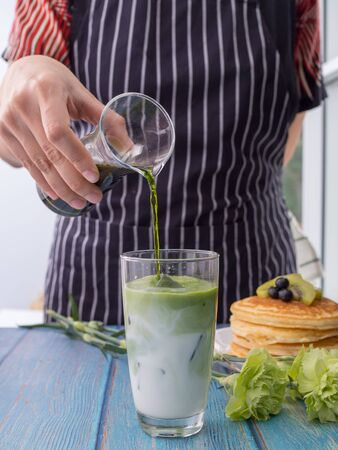 The bartender women are pouring green tea into a glass of milk. Green tea is eaten with pancakes. Tea mixed with milk in a glass. Food and drink concept Banque d'images - 131833784