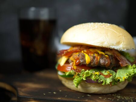 Homemade burgers with beer and  made of bacon, pork, tomato, lettuce, onion, cheese and spices on wooden background 写真素材