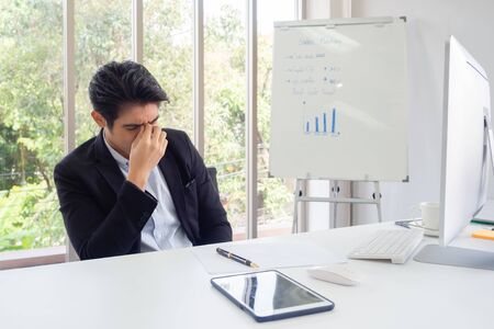 Businessman sit at a desk in an office green trees. He with his hand holding his face feel sad, worry, fatigue, frustration, irritability, failure after failure. Stockfoto