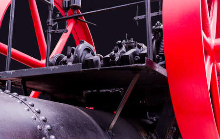 Close-up of vintage black and red railway machinery. Cut out the original background and overlap with the new black background. It was abandoned on the side of the road in Thailand.