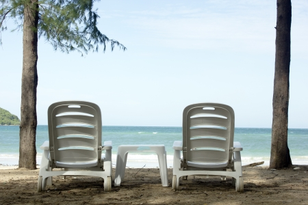 Two beach chairs and 2 parasols on the beach Stock Photo