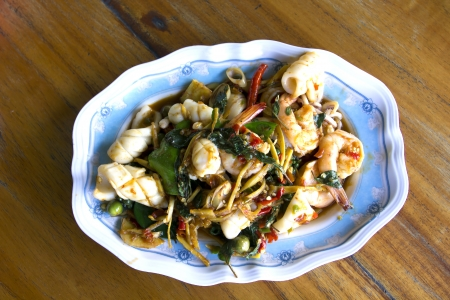 top view stir fried prawn and squid with mix vegetable on dish , spicy dish