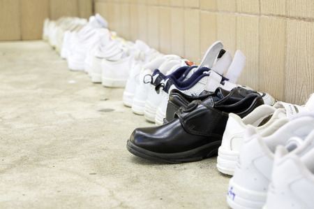 sort out: Arranged in an orderly school students shoes before entering the classroom in Thailand, but there is another one. Unique