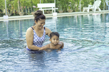 Beautiful mother teaching cute baby girl how to swim in a swimming pool. Child having fun in water with mom