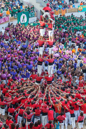 TARRAGONA, SPAIN - OCTOBER 6:  Members of \Colla Joves Xiquets de Valls \, build a traditional human tower at the Tarragona during the celebrations in Tarraco Arena Pla?a,  castles contest, October 6, 2012, Tarragona, Spain