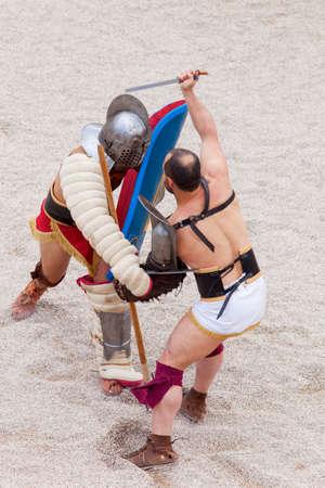 greco roman  roman: Tarragona, Spain - May 19, 2013: Gladiators on the arena of Roman Amphitheater on May 19, 2013 in Tarragona, Spain. Every year, the historic recreation program TarracoViva recreates a gladiators fight