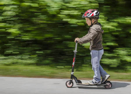 scooter: A boy with helmet riding his scooter on a sunny day