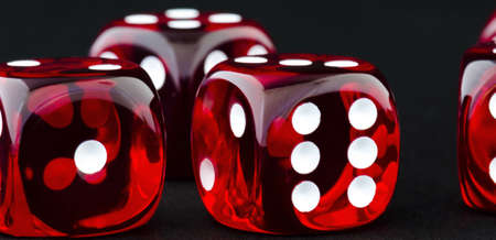 Shiny red dice with white dots in black background photo