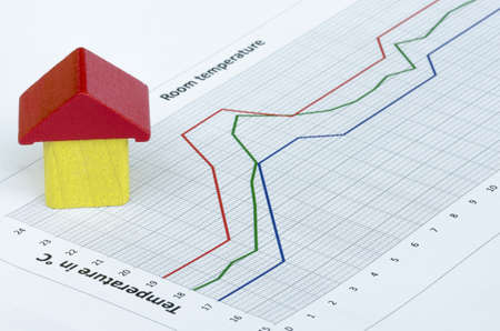 overheating: Wooden house build from wooden blocks on temperature graph Stock Photo