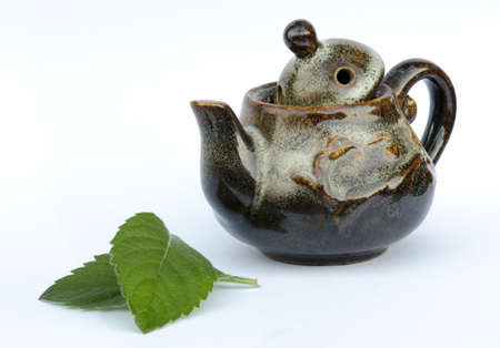 open minded: Teapot with mint leaves isolated on white background