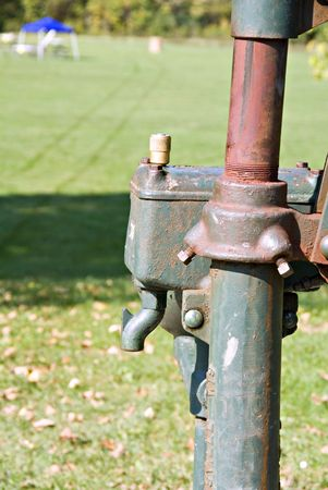 A part of an old fashioned water pump in a public park.