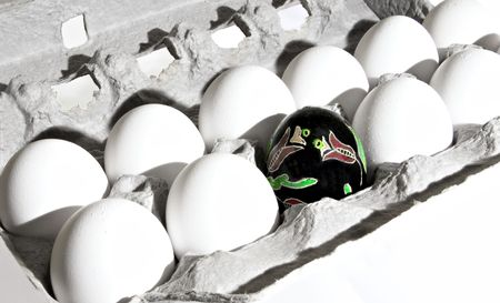ukranian: One Ukranian decorated egg that I created among ten uncolored chicken eggs.  Stock Photo