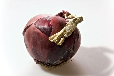 unsliced: A raw unsliced red onion with skin and stem.
