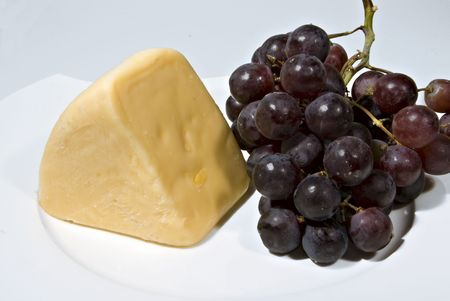 A wedge of cheese and bunch of red seedless grapes.