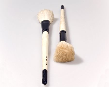 Two artists brushes showing the bristles and wooden handles.