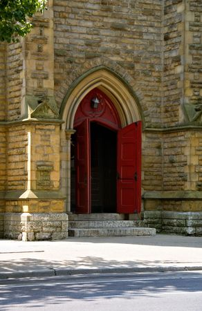A set of open red church doors against old brick wall.