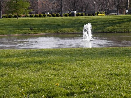 A metropolitan park scene with a pond and water feature.