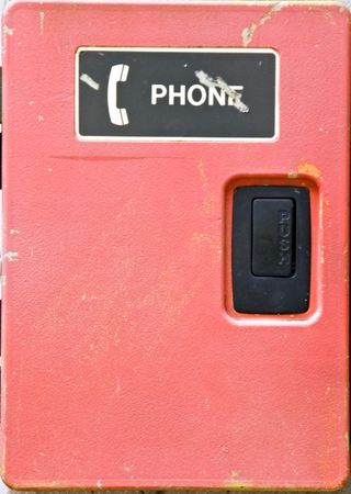 An emergency outdoor telephone box located on a brick wall.  Stock Photo