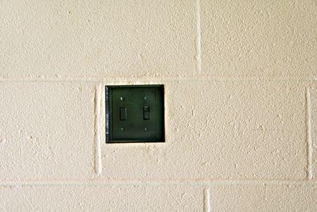 블록 벽에 조명 스위치입니다.