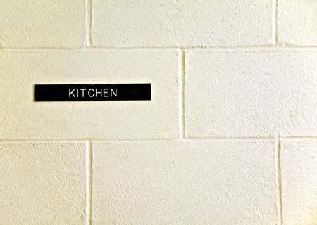 A sign on a wall with directions to the kitchen. Stock Photo
