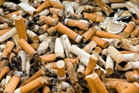 A bunch of used cigaretts butts and related trash.  Stock Photo