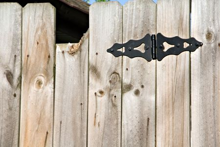 hinge joint: A wooden privacy fence with decorative black hinge.