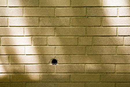 shadowed: A drilled hole in a shadowed brick wall.