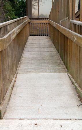 Een houten handicap helling leidt tot een openbare faciliteit. Stockfoto