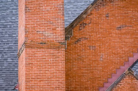 chimney corner: A close up view of a red brick building, chimney and slate roof.