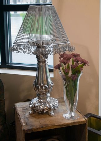 lamp shade: A table lamp with a decorative shade and sitting on a rustic table. Stock Photo