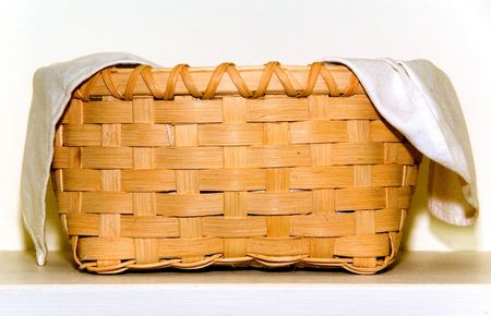 A wicker picknic basket with a cloth insert.