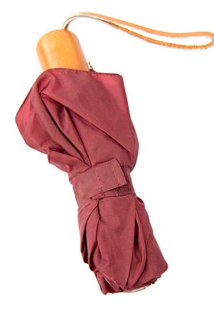 A well used umbrella that has been folded for storage.
