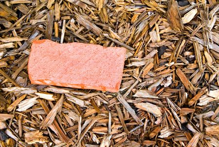 bark mulch: A red brick laying in a bed of wood mulch.