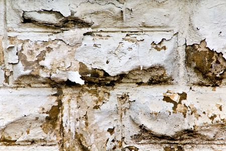Peeling white paint on a cement wall looking grungy and old.