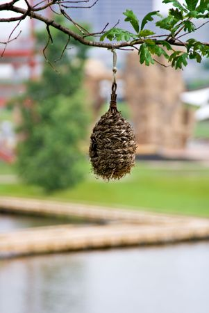 A bird house made of materals found in nature hanging in a tree.  Stock Photo
